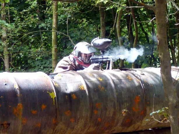 red attacking player behind paintball splattered barrels