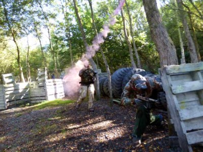 red attacking paintball player throwing a smoke grenade